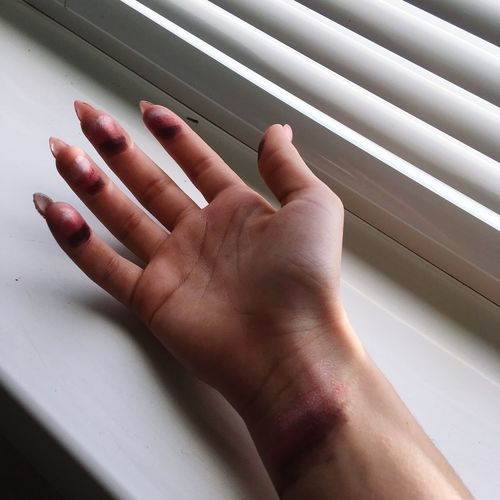 Cropped hand with make-up by window