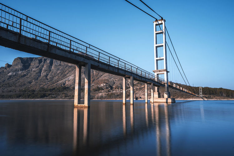 The longest suspension bridge in Bulgaria over Studen Kladenez dam with distance between the two towers of 260m. The only way to reach Lisicite village Reflection Water Sunset Nature Sky Bridge Travel Tower Lake Mountain Direction Pylon Way Suspension Dam Bulgaria Metal Overcast Wooden Suspension Bridge Longest Warm Clothing Bridge - Man Made Structure Transportation Connection Waterfront Architecture River Built Structure Clear Sky No People Day Blue Tranquil Scene Fuel And Power Generation Outdoors