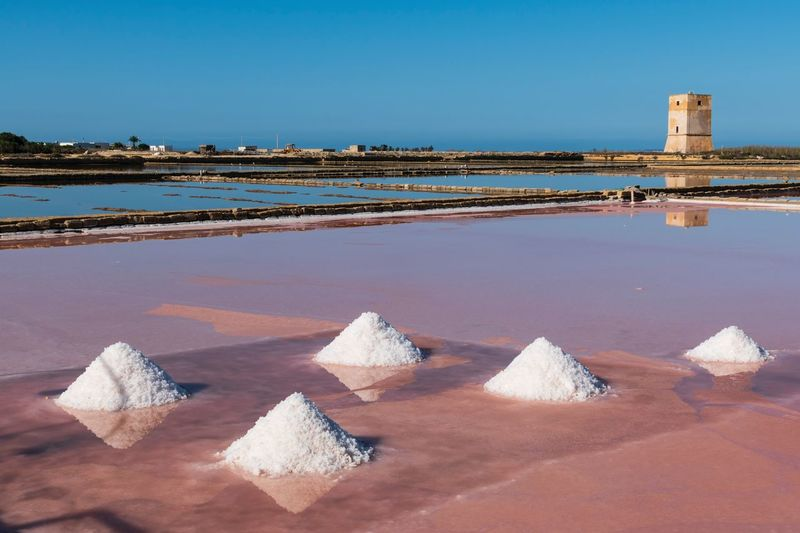 Scenic view of sea and salt  against clear blue sky