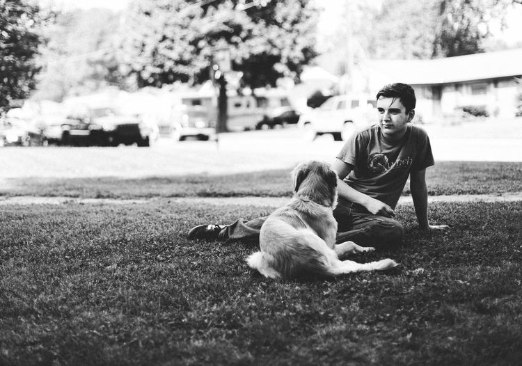 Man with dog sitting on grass