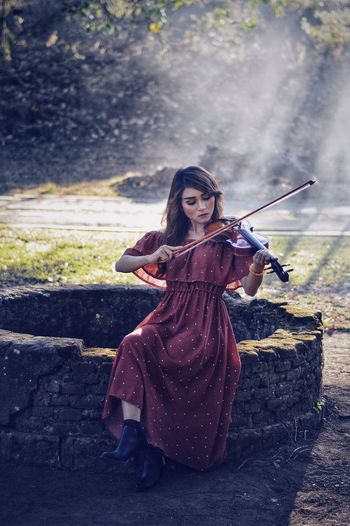 Woman playing violin while sitting on well