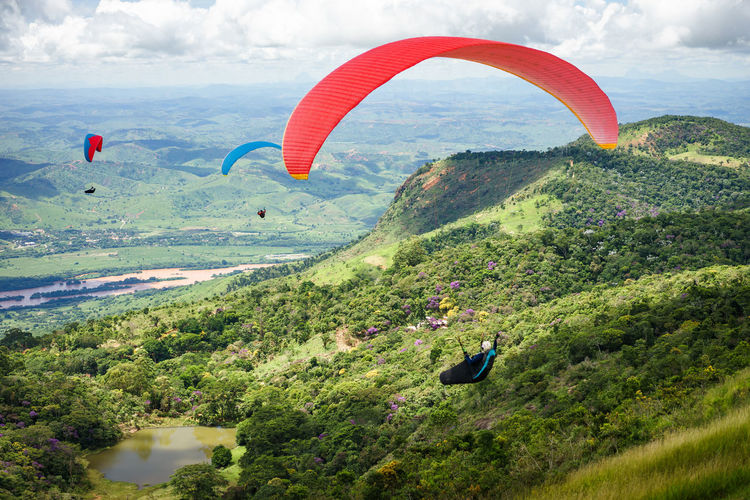 Paraglider is flying in Brazil. Brazil Adventure Beauty In Nature Cloud - Sky Day Environment Exhilaration Extreme Sports Flying Freedom Gliding Joy Leisure Activity Mid-air Nature Outdoors Parachute Paragliding Red Color Sky Skydiving Sport Transportation Unrecognizable Person Valadares