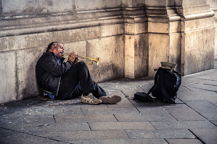 Senior street musician playing musical instrument while sitting on street