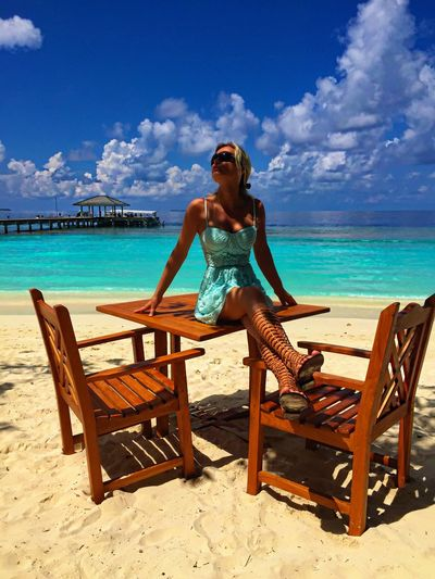 Woman sitting on table at beach against sky