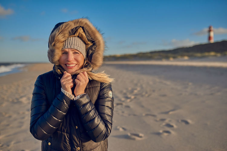 Happy woman walking at the beach Autumn Copy Space Woman Best Ager Day Focus On Foreground Front View Happiness Leisure Activity Lifestyles Middle-aged One Person Outdoors Real People Smiling Standing Upper Body Walking
