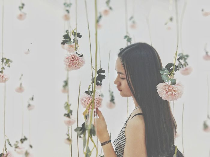 Woman standing amidst floral decoration
