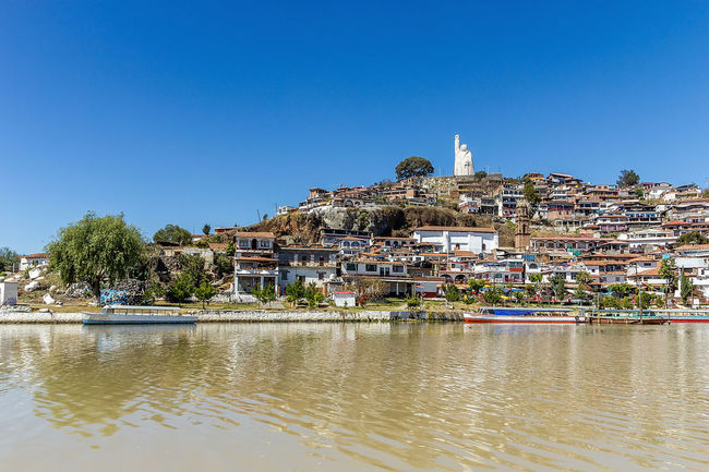 The Island of Janitzio in Lake Patzcuaro, Michoacan, Mexico Blue City City Life Clear Sky Copy Space Day Distant In Front Of Island Janitzio Jose Morelos Outdoors Residential District River Riverbank Statue Steeple Tourism Town Travel Destinations Tree Water Waterfront