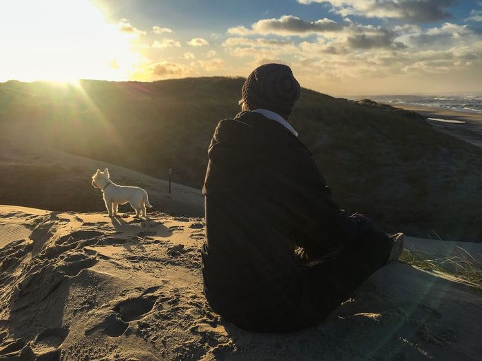 Rear view of man with dog sitting on landscape against sky during sunset