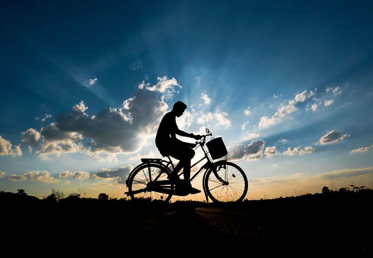 Silhouette man riding bicycle against cloudy sky during sunset