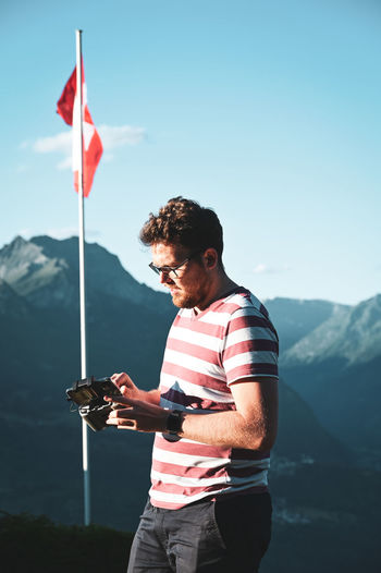 Young man using drone remote control against sky and mountains