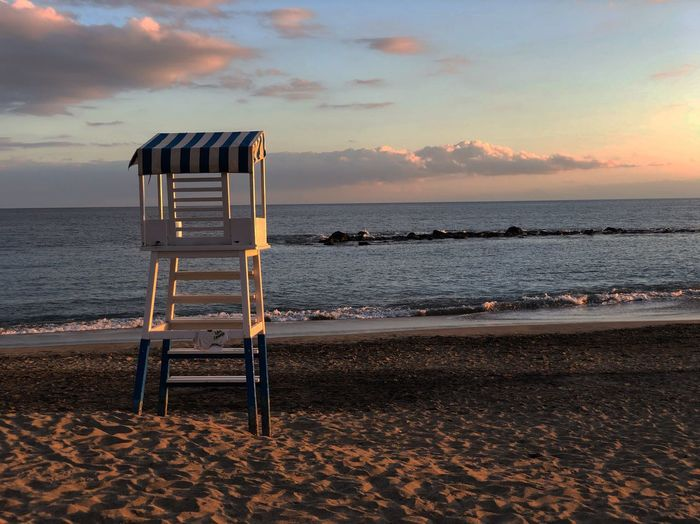 Lifeguard chair on beach against sky during sunset