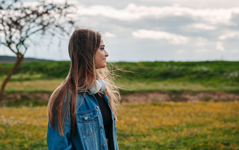 Woman contempling the landscape. Beautiful Woman Casual Clothing Contemplation Day Field Focus On Foreground Hair Hairstyle Land Leisure Activity Lifestyles Long Hair Nature One Person Outdoors Plant Real People Standing Women Young Adult Young Women