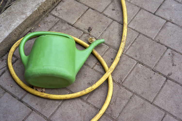 High angle view of watering can and hose on footpath