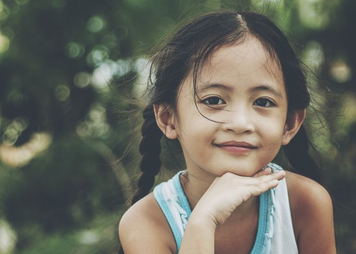 Close-Up Portrait Of Smiling Girl With Hand On Chin Sitting At Park