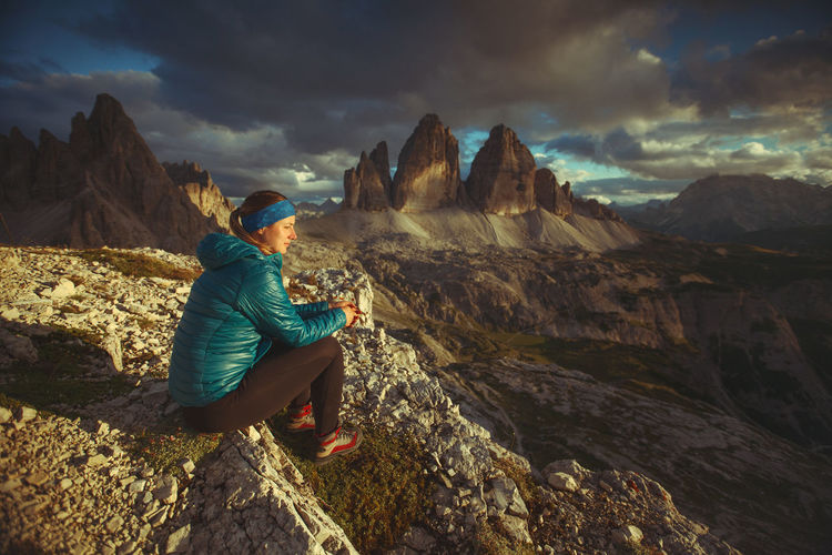 Side view of female hiker sitting on mountain against cloudy sky during sunset