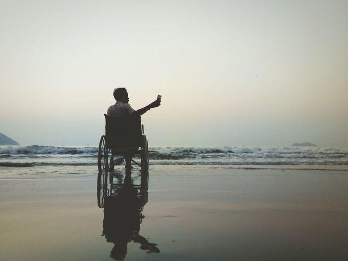 Man taking selfie while sitting on wheelchair at beach during sunset
