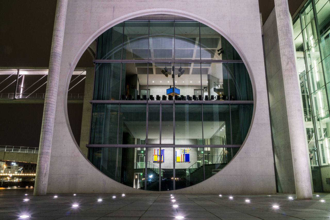 architecture, built structure, reflection, group of people, glass - material, city, transparent, men, people, building exterior, real people, modern, illuminated, incidental people, building, outdoors, women, window, geometric shape, circle