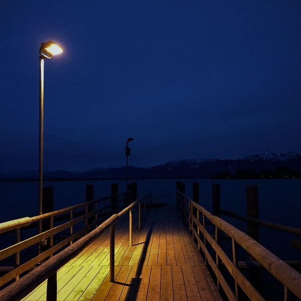 Light Nightphotography Beauty In Nature Chiemsee Illuminated Jetty Light And Shadow Lighting Equipment Mountain Mountain Range Mountains Mountains And Sky Nature Night No People Outdoors Pier Railing Scenics Sea Sky Street Light Tranquil Scene Tranquility Water
