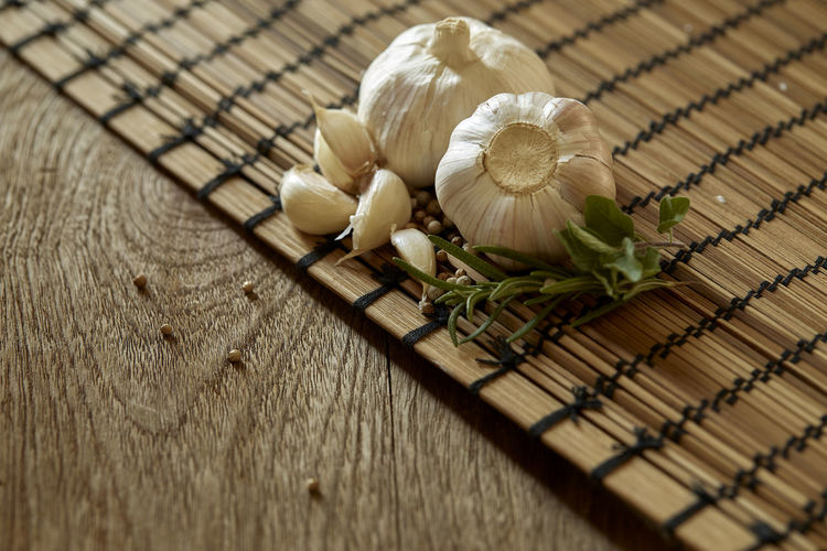 High Angle View Of Garlic And Peppercorns With Herbs On Wooden Table