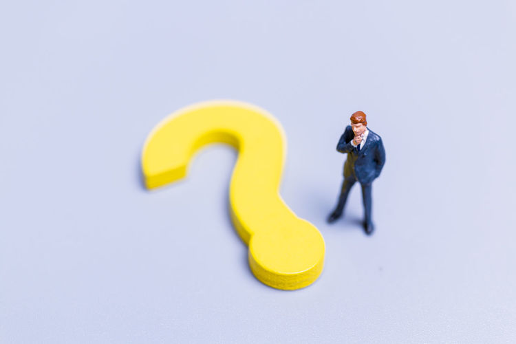 Man with yellow toy against white background