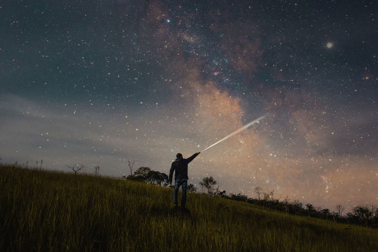 Rear view of man holding flashlight on land against star field