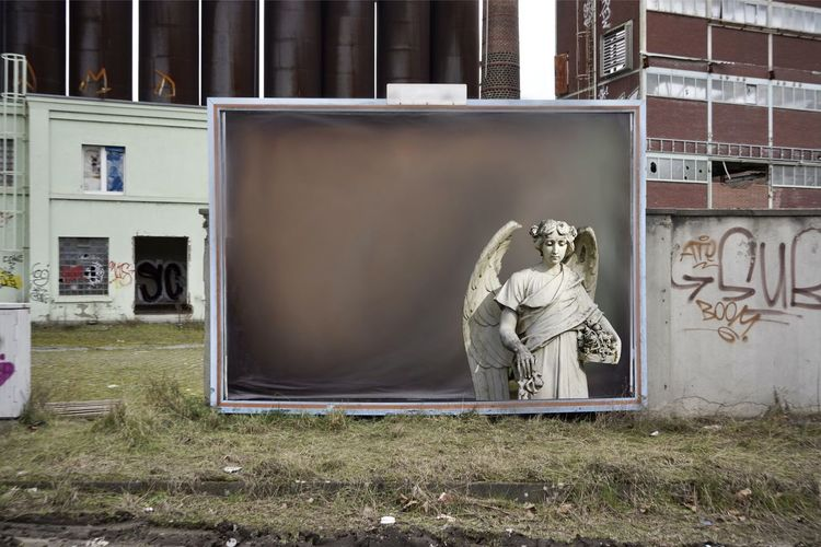 Statue against abandoned building