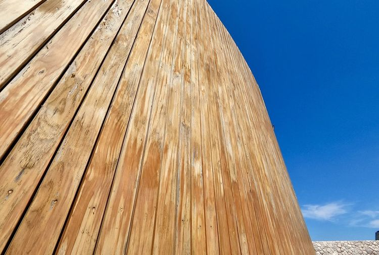Low angle view of wooden wall against blue sky