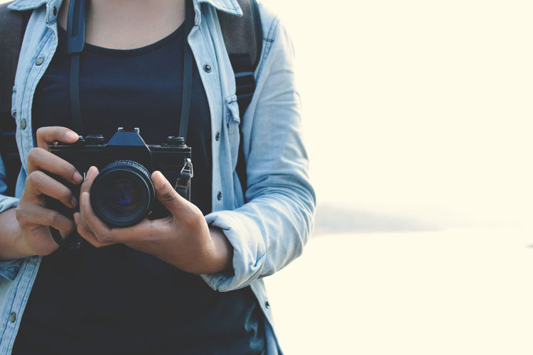 Midsection of woman holding camera while standing against lake