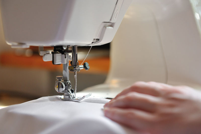 Cropped Image Of Hand Sewing On Machine