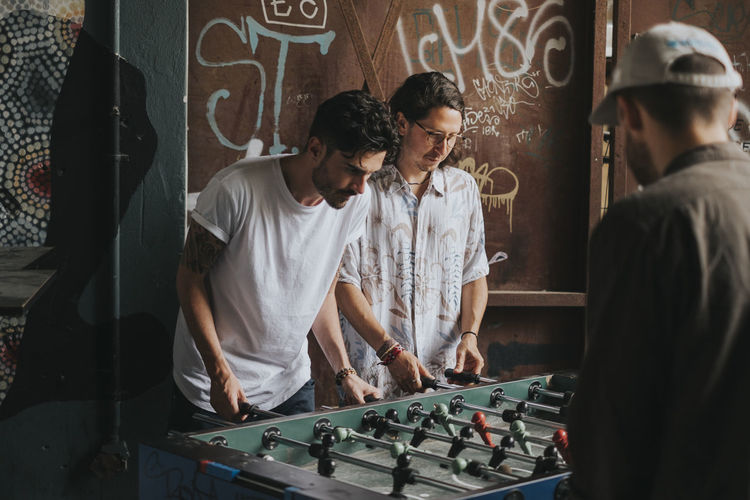 Friends playing foosball against graffiti wall at club