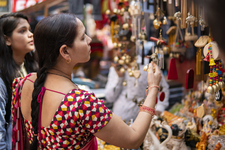 Mother daughter by decoration at market stall