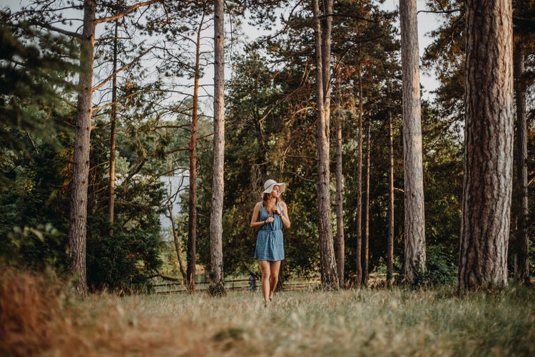 Woman walking on grass in forest