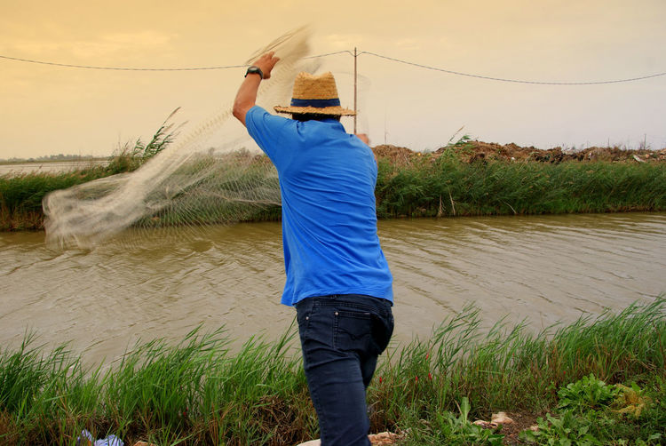 Rear view of man fishing in river against sky
