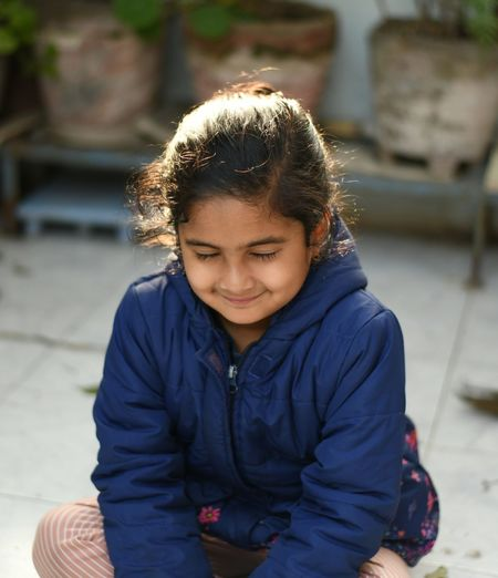 Smiling girl with closed eyes sitting outdoors