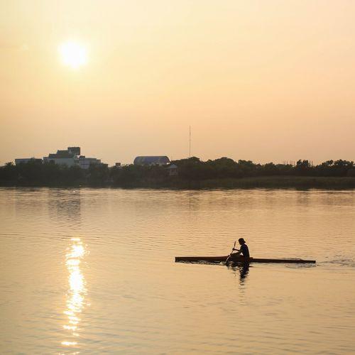 Man Rowing Raft In Lake During Sunrise