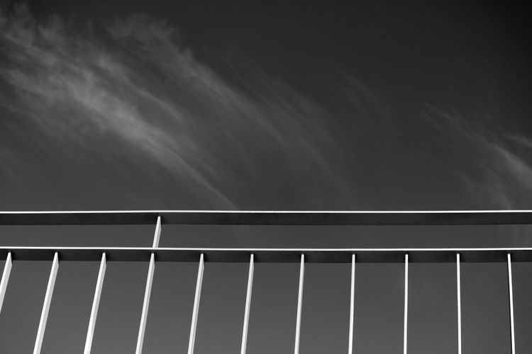 Low angle view of railing against sky