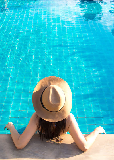 Midsection of woman relaxing in swimming pool