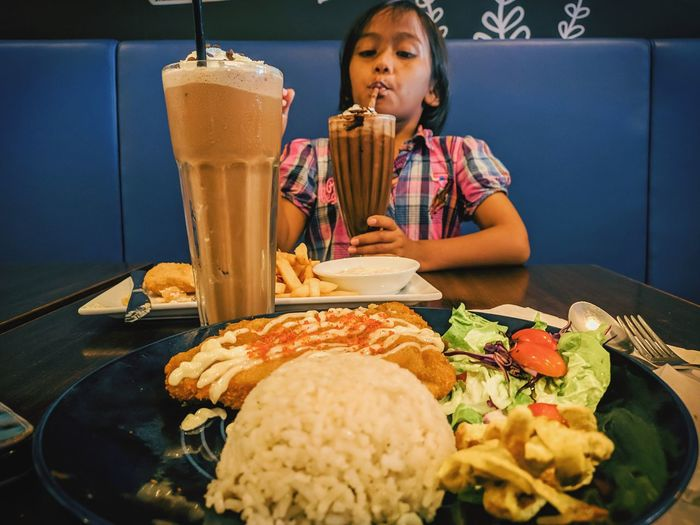 Cute girl enjoying food and drinks served on table in restaurant