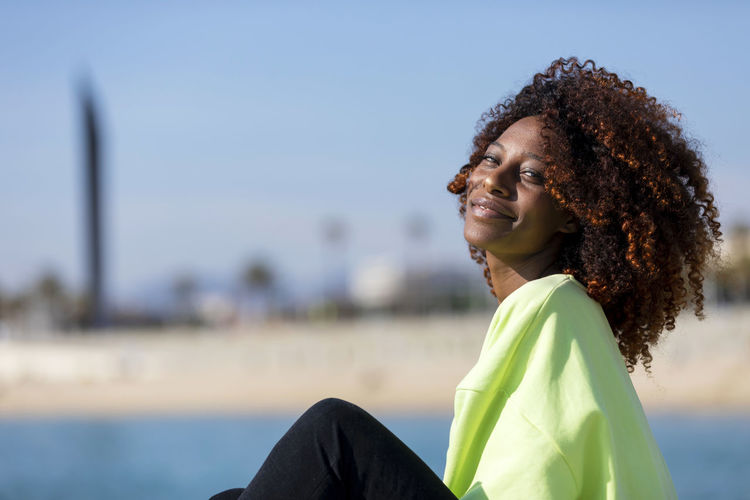 Side view of beautiful curly afro woman sitting on breakwater rocks laughing while looking camera outdoors Smiling One Person Curly Hair Happiness Side View Portrait Women Young Adult Casual Clothing Focus On Foreground Leisure Activity Young Women Sitting Real People Emotion Relaxation Day Looking Hairstyle Hair Beautiful Woman Contemplation Woman African American Afro Denim Happiness Happy Fun Daylight Sunlight