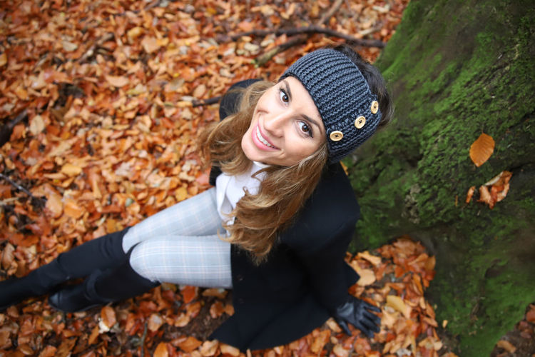Young woman smiling with leaves during autumn