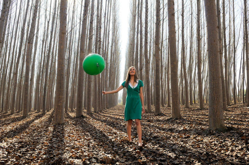 Full length of woman holding balloon while standing in forest