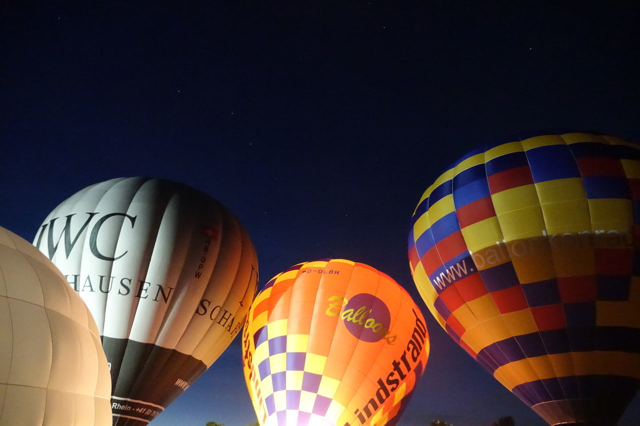 hot air balloon, night, low angle view, celebration, multi colored, outdoors, ballooning festival, flying, no people, sky