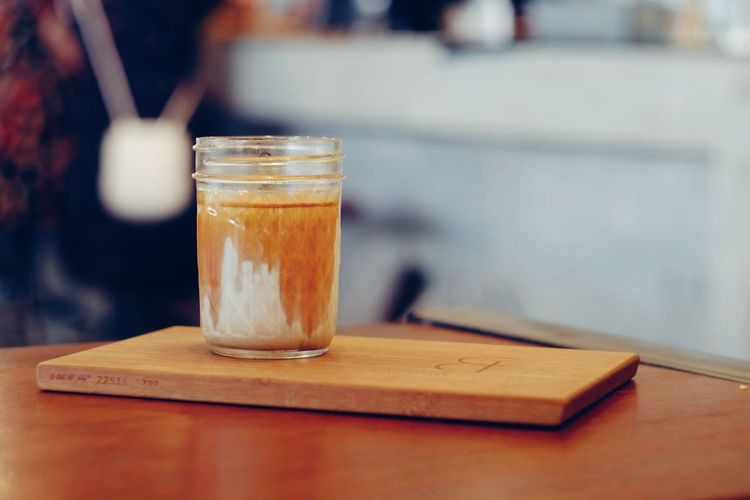 Glass of dirty coffee on wood table Cold Drink Glass Fresh Refreshment Cappuccino Sugar Latte Sweet Drink Barista Beverage Caffeine Aroma Breakfast Break Business Relax Cafe Coffee Morning Coffee Cup Dirty Coffee Cold Still Life Shop