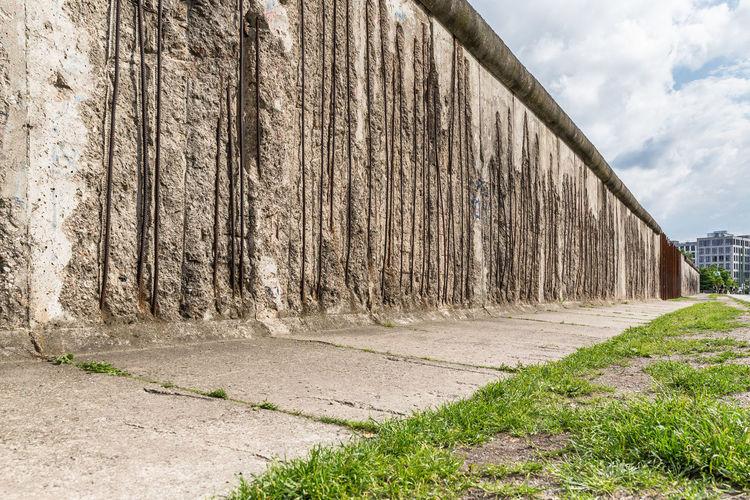 Damaged historic berlin wall against sky