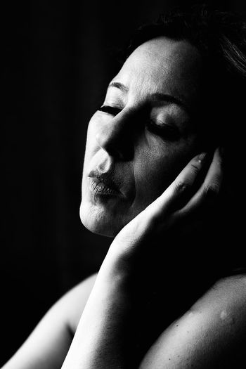 Close-up of woman with closed eyes sitting against black background
