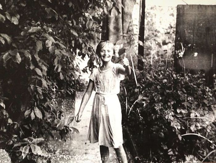 Portrait of smiling girl standing against plants