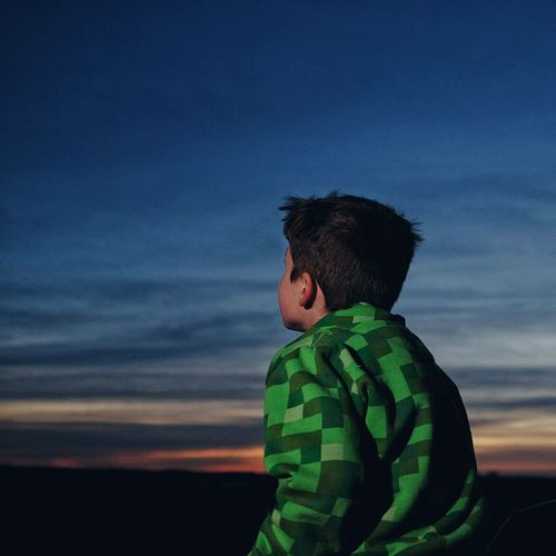 Low Angle View Of Boy At Field Against Sky At Dusk