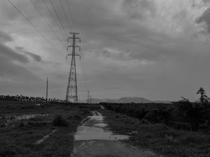 Electricity Pylons Against Cloudy Sky
