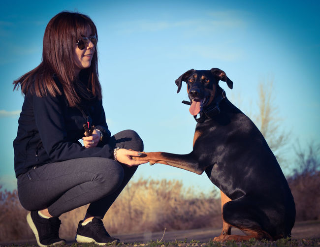 Woman with dog sitting against sky