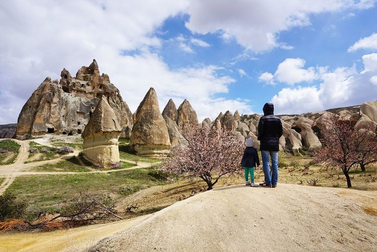 Rear view of mother standing with daughter on field at cappadocia